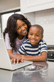 Mother and son using laptop. In the kitchen stock photography