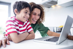 Mother and son using laptop in kitchen. At home royalty free stock image
