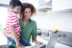 Mother and son using laptop in kitchen. At home royalty free stock photos