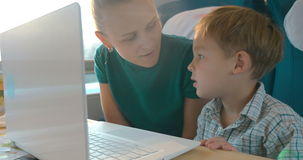 Mother and son using laptop in the train. Mother and son using laptop for entertainment speaks during the travel by train stock footage