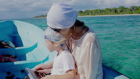 Mother and son using pad while traveling by sea. Mother and little son sailing on boat in quiet blue sea and using tablet computer stock footage