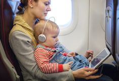 Mother and son using tablet on board of airplane Stock Image