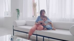 Mother and son using tablet looking at screen and talking on sofa in cozy house. Mother and son using tablet looking at screen and talking on sofa in cozy house stock footage