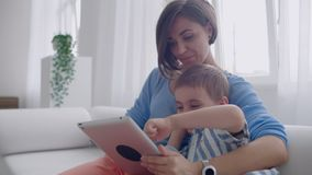 Mother and son using tablet looking at screen and talking on sofa in cozy house. Mother and son using tablet looking at screen and talking on sofa in cozy house stock video