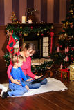 Mother and son using tablet pc by a fireplace Stock Photography
