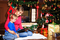 Mother and son using tablet pc by a fireplace Stock Images