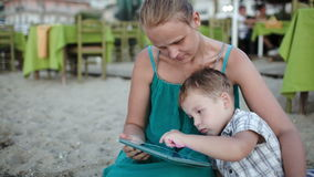 Mother and son using tablet PC near beach cafe. Mother and son sitting on the sand near cafe on the beach. Boy using pad, mother watching and kissing him stock footage
