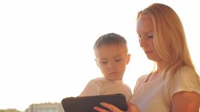 Mother and son using tablet on vacation at sunset. Mother and son using tablet on vacation at sunse stock footage