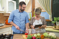 Mother and son using touchpad and preparing food in kitchen. Stock Photos