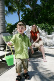 Mother and son on vacation. Boy with beach pail and woman watching in the background, tropical resort setting Stock Photos