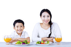 Mother and son with vegetable salad. Portrait of happy mother and son having vegetable salad. isolated on white background Stock Images