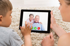 Mother And Son Videoconferencing On Digital Tablet Royalty Free Stock Images