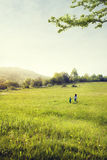 Mother and son walk in field. Nature landscape with green grass Stock Image