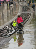 Mother and son walk in Manchester under rain. Typical English weather in Manchester, mother walks out her son on the broken stone pathway, with some pedestrians Royalty Free Stock Images