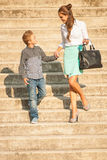 Mother and son walk on stairs in city on late summer afternoon Stock Photos