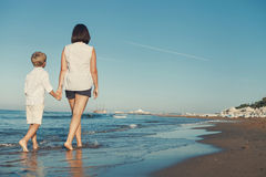 Mother with son walk together on surf sea line Stock Image