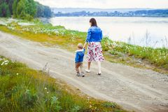 Mother and son walking on country road. Mother and son walking along a country road near the river stock photos