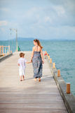 Mother and son walking along jetty Stock Photo
