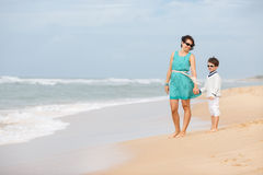 Mother and son walking along a tropical beach Royalty Free Stock Photo
