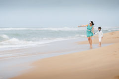 Mother and son walking along a tropical beach Stock Image