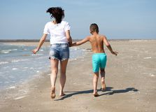 Mother and son walking barefoot Stock Photos