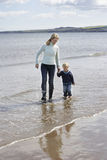 Mother And Son Walking On Beach Stock Photography