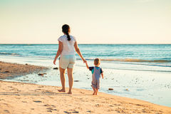 Mother and son walking on beach Stock Image