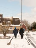 Mother and son walking down street with snow in winter uk estate royalty free stock photography