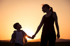 Mother and son walking on the field at the sunset time. People having fun outdoors. Concept of friendly family Royalty Free Stock Photos