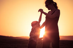 Mother and son walking on the field at the sunset time. People having fun outdoors. Concept of friendly family Royalty Free Stock Images