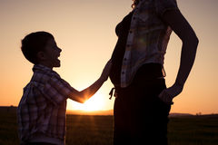Mother and son walking on the field at the sunset time. People having fun outdoors. Concept of friendly family Stock Photos