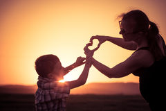 Mother and son walking on the field at the sunset time. People having fun outdoors. Concept of friendly family Royalty Free Stock Image