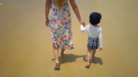 Mother and son walking on foot along the beach near the ocean. Mother and son walking on foot along the beach near the ocean Royalty Free Stock Photos