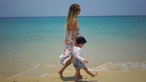 Mother and son walking on foot along the beach near the ocean. Mother and son walking on foot along the beach near the ocean Stock Photos