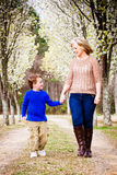 Mother and son walking hand in hand at park Stock Images
