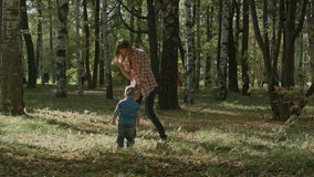 Mother with son walking outdoor in autumn. Shot on BMCC. You can use it e.g in your video, documentalistic, reporting, presentation, music video, commercial stock video