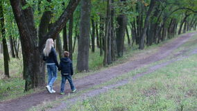 Mother and son walking in the park. Holding hands. Happy family concept stock footage