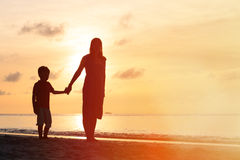 Mother and son walking on sunset beach Stock Image