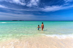 Mother and son walking towards white sandy Cuban beach in Cayo Coco Royalty Free Stock Photography