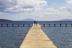 Mother and son walking on a wooden pier background with blue sky Stock Image