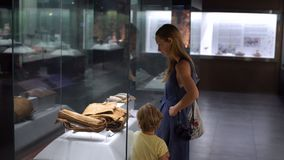 Mother and son watch historical exposition in natural history museum.  stock video
