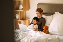 Mother and son watching cartoons on laptop in bed. Young mother with her beloved son in the bedroom on the bed watching a movie on laptop. Adorable boy sitting royalty free stock photo