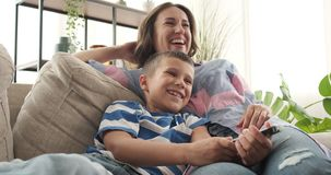 Mother with son watching comedy on tv. Relaxed mother and son laughing while watching comedy on tv stock video footage