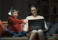 Mother and son watching movies on a laptop stock photography