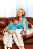 Mother and son watching television with popcorn Royalty Free Stock Photography