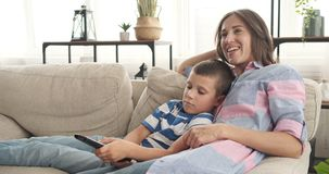 Mother with son watching tv at home stock footage