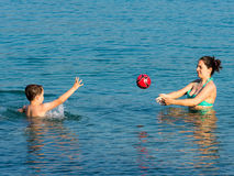 Mother and son in the water. Mother and son having fun in the water during summer holidays, playing with a ball Royalty Free Stock Photo