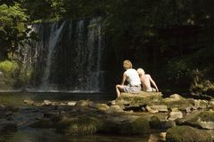 Mother and son by waterfall. Rear of of young mother and son sitting by waterfall in countryside royalty free stock photo