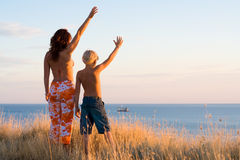 Mother and son wave hands. Happy mother and son wave hands at sunset Royalty Free Stock Photos
