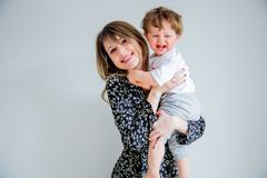 Mother and son on a white wall background at home stock images